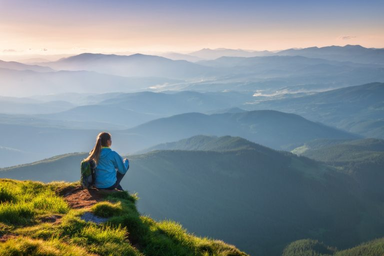Woman with backpack sitting on the mountain peak at sunset